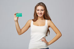 Fille de sourire heureuse dans les vêtements décontractés, montrant la carte de crédit en blanc Photo stock
