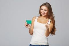 Fille de sourire heureuse dans les vêtements décontractés, montrant la carte de crédit en blanc Image libre de droits