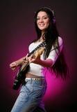 Fille de sourire heureuse jouant la guitare Photographie stock libre de droits