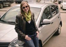 Fille de sourire heureuse se tenant près de la voiture Image libre de droits
