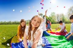 Fille de sourire jouant avec des amis en parc Photo stock