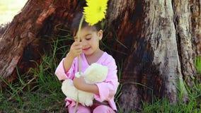 Fille de sourire jouant avec une fleur et un ours de nounours banque de vidéos