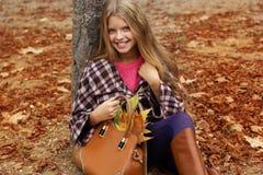 Fille de sourire mignonne avec le sac plein des feuilles d'automne photo stock
