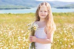 Fille de sourire mignonne d'enfant au champ de camomille photographie stock libre de droits