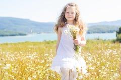 Fille de sourire mignonne d'enfant au champ de camomille photos libres de droits