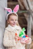 Fille de sourire mignonne dans un masque de lièvres pour la célébration du jour international de Pâques Image stock