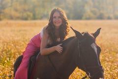 fille de sourire montant un cheval dans un rose photographie stock