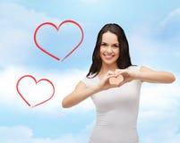 Fille de sourire montrant le coeur avec des mains Image libre de droits