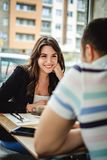 Fille de sourire parlant à son ami dans le restaurant Photos libres de droits