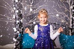 Fille de sourire parmi les flocons de neige en baisse Image stock