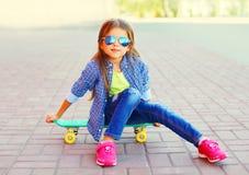 Fille de sourire de portrait élégant petite s'asseyant sur la planche à roulettes photo libre de droits