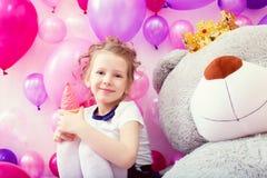 Fille de sourire posant avec la crème glacée dans la salle de jeux Photos stock