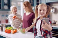 Fille de sourire prenant le selfie tandis que cuisson de mère et de grand-mère Photographie stock