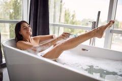 Fille de sourire rasant ses jambes dans le bain avec la mousse image libre de droits