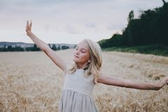 Fille de sourire s'étirant dans un domaine de blé Image libre de droits