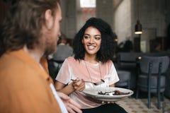 Fille de sourire s'asseyant dans le restaurant avec l'ami Belle dame d'Afro-américain s'asseyant au café avec de la salade à disp Photographie stock