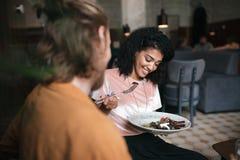 Fille de sourire s'asseyant dans le restaurant avec l'ami Jolie dame d'Afro-américain s'asseyant au café avec le plat de la salad Photos libres de droits