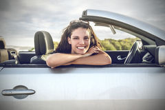 Fille de sourire s'asseyant dans une voiture Photographie stock libre de droits