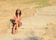 Fille de sourire s'asseyant sur des escaliers Photographie stock