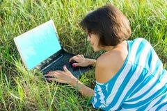 Fille de sourire s'asseyant sur l'herbe dans le jour d'été lumineux et travaillant sur l'ordinateur Photos stock