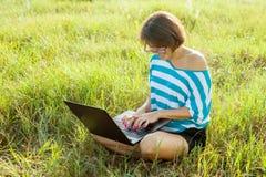 Fille de sourire s'asseyant sur l'herbe dans le jour d'été lumineux et travaillant sur l'ordinateur Utilisant l'ordinateur portab Photos stock