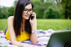 Fille de sourire s'asseyant sur l'herbe dans le jour d'été lumineux et travaillant sur l'ordinateur Utilisant l'ordinateur portab Image stock