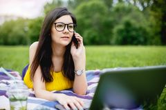 Fille de sourire s'asseyant sur l'herbe dans le jour d'été lumineux et travaillant sur l'ordinateur Utilisant l'ordinateur portab Photo stock