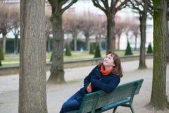 Fille de sourire s'asseyant sur un banc en stationnement Image libre de droits