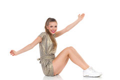 Fille de sourire s'asseyant sur un plancher avec des bras tendus Images libres de droits