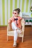 Fille de sourire s'asseyant sur une chaise Image stock
