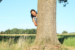 Fille de sourire se cachant derrière l'arbre Photo libre de droits