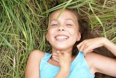 Fille de sourire se trouvant sur l'herbe Images libres de droits
