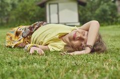 Fille de sourire se trouvant sur l'herbe verte et apprécier la chaleur d'été Image libre de droits