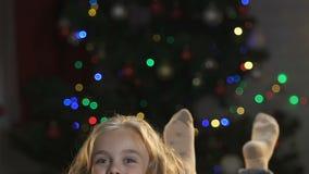 Fille de sourire se trouvant sur le fond de l'arbre de Noël, ondulant heureusement ses jambes banque de vidéos
