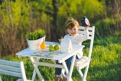 Fille de sourire tenant l'horloge Photographie stock libre de droits