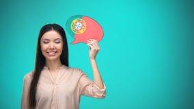 Fille de sourire tenant la bulle portugaise de la parole de drapeau apprenant l'idée de voyage de langue banque de vidéos