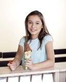 Fille de sourire tenant le cornet de crème glacée de chocolat au compteur image stock