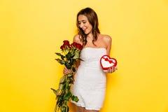 Fille de sourire tenant les roses et le boîte-cadeau de son ami le jour du ` s de Valentine Image stock