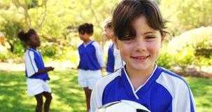 Fille de sourire tenant un football en parc banque de vidéos