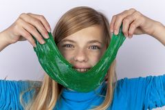 Fille de sourire tenant un jouet vert de boue devant son visage photos stock