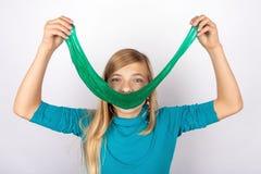 Fille de sourire tenant un long jouet vert de boue devant son visage photographie stock