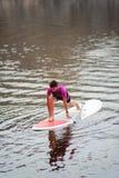 Fille de sports faisant étirant des exercices sur le panneau de ressac à partir du rivage photographie stock