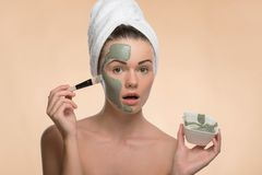 Fille de station thermale avec une serviette sur sa tête appliquant le massage facial Photo stock