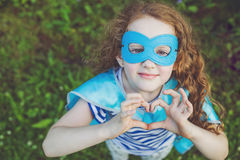 Fille de super héros montrant des mains dans la forme de coeur Image stock