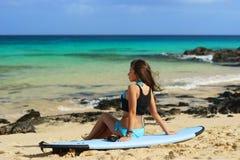 Fille de surfer s'asseyant sur la planche de surf à la plage Photographie stock