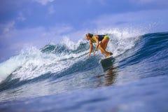 Fille de surfer sur la vague bleue étonnante Photo stock