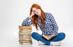 Fille de Thoghtful s'asseyant et se penchant sur la pile des livres Photographie stock libre de droits