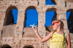 Fille de touristes avec le petit fond Colosseum d'avion modèle de jouet à Rome, Italie Photo stock