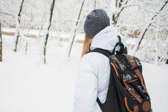 Fille de touristes avec le sac à dos presque se tenant à l'entrée d'un hôtel, voyage au concept de nouvelle année Image libre de droits