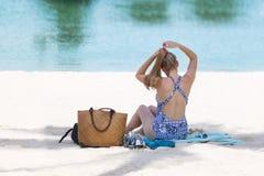 Fille de touristes blonde dans le bikini détendu et le prenant un bain de soleil sur la plage photos libres de droits